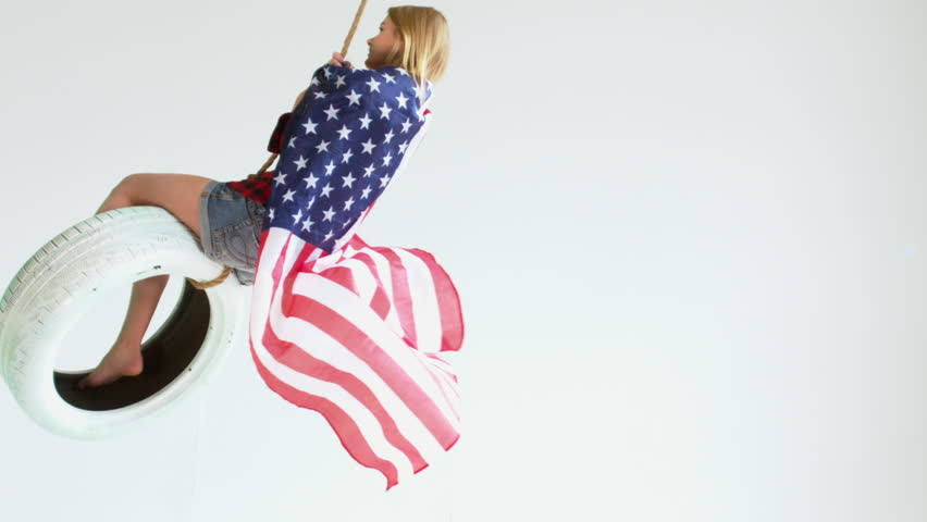 Wide shot of young Caucasian girl with waving American flag riding on a tire swing against white background. 1080 HD 120 FPS Slow motion. Shot with Blackmagic URSA Mini