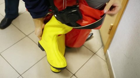 Showing of protective suit - disrobing of rubber shoes