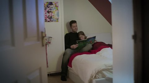 Father reads a story book to his young daughter in a bed in daughter's bedroom. Father with short dark hair and young girl with long brown hair. Girl looks sleepy. Filmed through door on a wide in 4K.