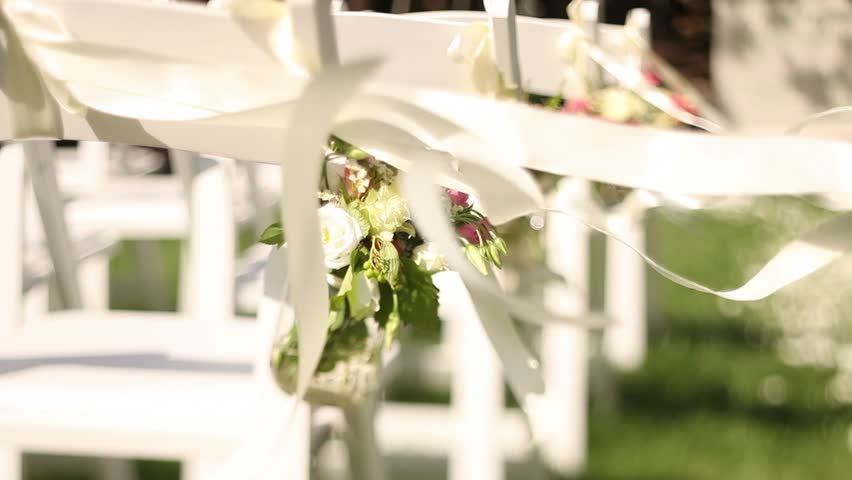 Wedding decor on the chairs , ribbons and flower on white chairs , roses and wild flowers in small vases in the wedding decor , satin ribbons are developed in the wind
