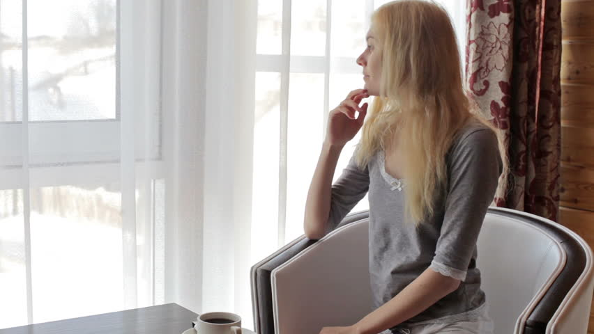 Girl drinking coffee while sitting in a chair by the window | Shutterstock HD Video #14833201