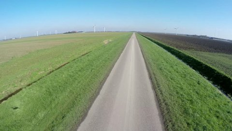 Aerial drone flying very low and fast over polder grassland very straight road on left grassland and on right side dark brown black plowed land very blue crisp sky spring day wide rural landscape