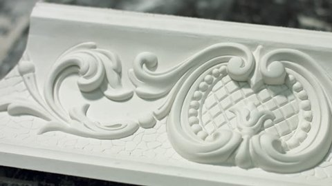 Close-up of a clay cornice. Charming floral ornament. Ornament on cornice. The craftsman re-created ancient style.
