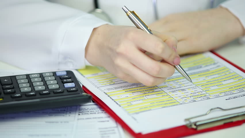 Female therapist filling out health insurance claim form, calculating expenses