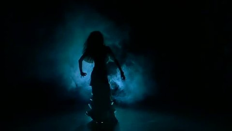 Beautiful exotic belly dancer girl shaking her hips, on black, slow motion, silhouette, smoke