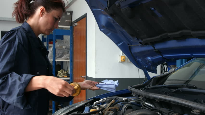Female mechanic checking oil in the engine in the garage