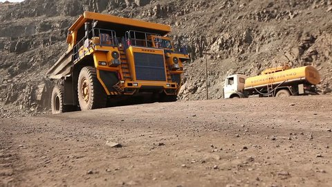 Heavy mining truck on the iron ore opencast mining quarry, big truck carries cargo in career, industrial exterior, ore mining quarry, sunny day, summer
