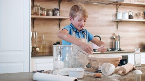 young boy home alone and trying to make a cake, making a huge mess in the kitchen clapping flour everywhere