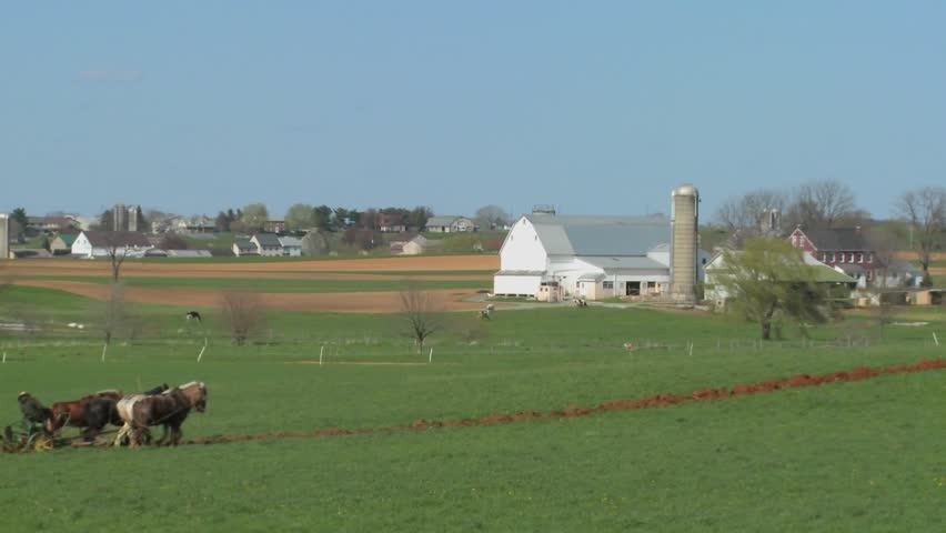 Amish country with farmer farming the land.