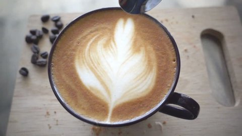 Stiring milk foam in a cup of latte coffee, slow motion