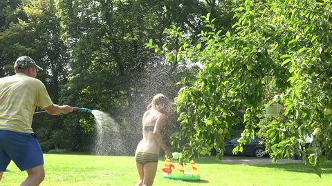 Playful couple boy and girl lifestyle in sunny hot summer day. Man guy catch and spray woman girl in underwear with water hose in garden yard. Static shot.