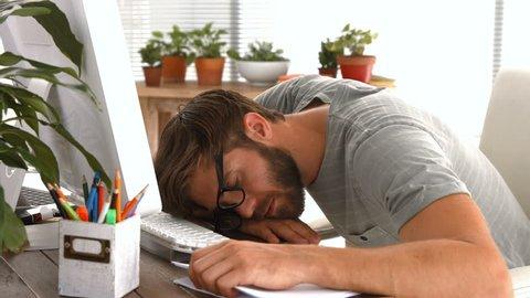 Casual businessman sleeping on desk in office