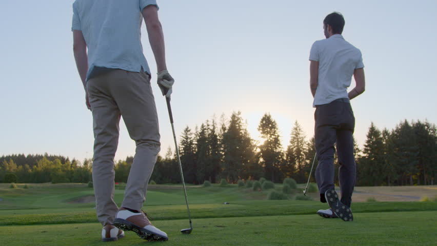 Two golfers high five after taking their tee shot