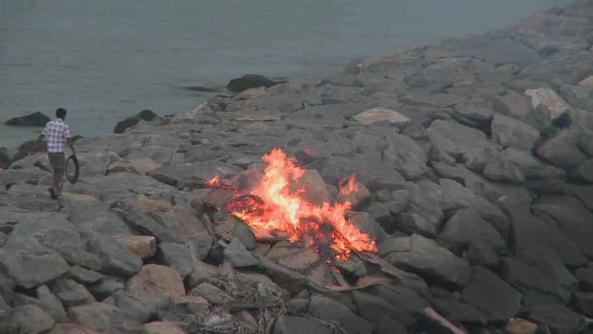 INDIA - CIRCA 2010: A man throws a piece of rubbish into a burning fire circa 2010 in India. Water supply and sanitation in India continue to be inadequate, despite longstanding efforts by the various levels of government and communities at improving cove