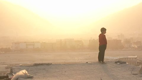 KABUL, AFGHANISTAN - CIRCA 2009: A boy looks out during a dust storm circa 2009 in Kabul, Afghanistan. Afghanistan is an impoverished and least developed country, one of the world's poorest.