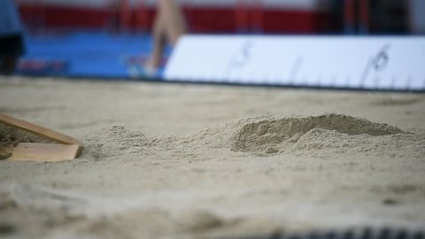Men raking the sand after a long jump in the sandpit