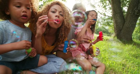 Cute african-american family sitting in a gorgeous picturesque park while playing with their kids and blowing bubbles on a beautiful sunny afternoon