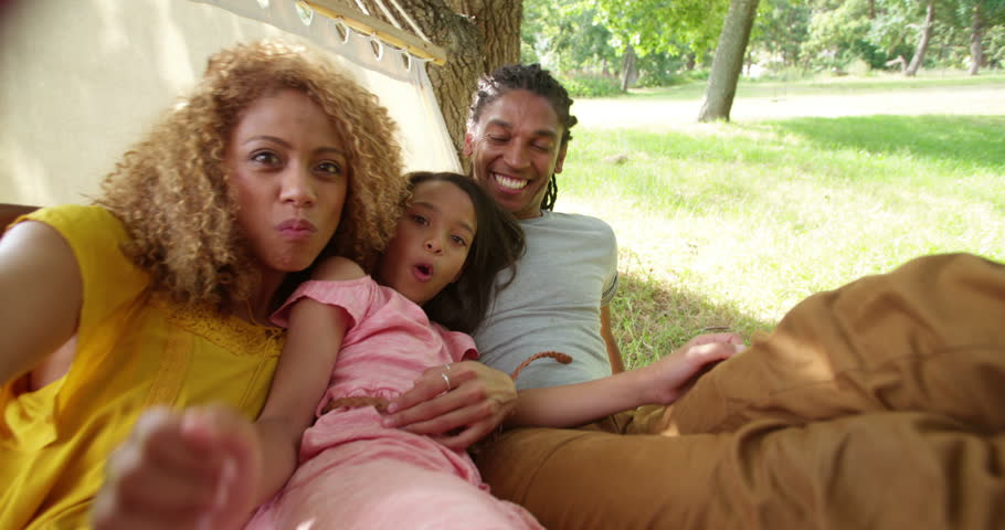 Attractive Multi-ethnic mother and father spends quality time with their adorable daughter, taking wacky selfies and swinging around on a hammock outdoors in nature.