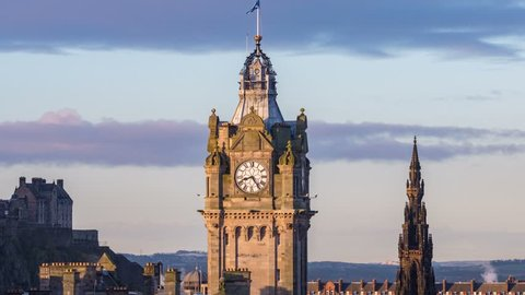 Time lapse footage of the Balmoral Clock at sunrise, viewed from Calton Hill. Edinburgh Castle and the Walter Scott Monument in the background.  Edinburgh, Scotland