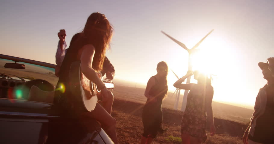 Caucasian young adult woman playing guitar oudoor on a summer sunset with friends and sings