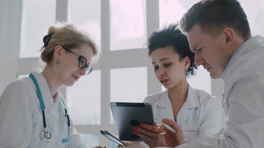 Healthcare, medical: Team of experts multi-ethnic doctors examining medical exams in a medical office | Shutterstock HD Video #15127477