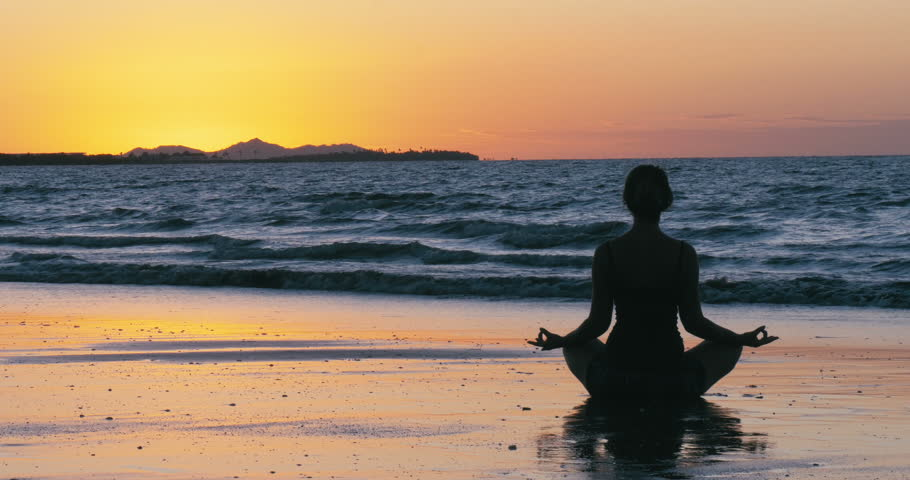 Silhouette young woman practicing yoga on the beach in fiji  at sunset healthy life, new years resolution, healthy mind