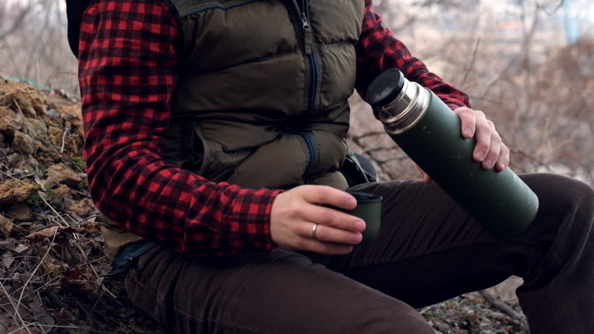 Traveler pours and drinks hot tea or coffee at rest, during his walks in the woods, forest. Man hiking, resting on the nature. The traveling men, tourist, traveler, explorer sitting outdoors.