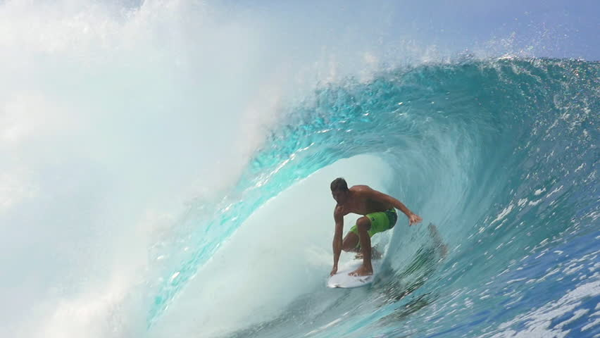SLOW MOTION CLOSE UP: Cheerful extreme pro surfer surfing big tube barrel wave Teahupoo in crystal clear Pacific ocean in sunny Tahiti island