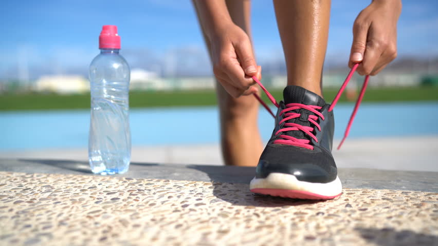 Sports woman runner getting ready for run tying laces of running shoes next to water bottle on athletic track and field background. Female athlete preparing for fitness cardio workout. Feet closeup.