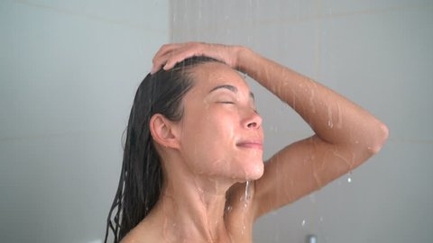 Woman showering washing hair in hot water. Happy young adult relaxing enjoying luxury bathtime cleaning her face and rinsing her body in hotel shower or at home in her private bathroom.