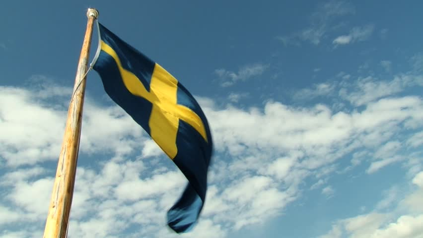 Swedish National flag waves with the blue sky at the background in Stockholm, Sweden.