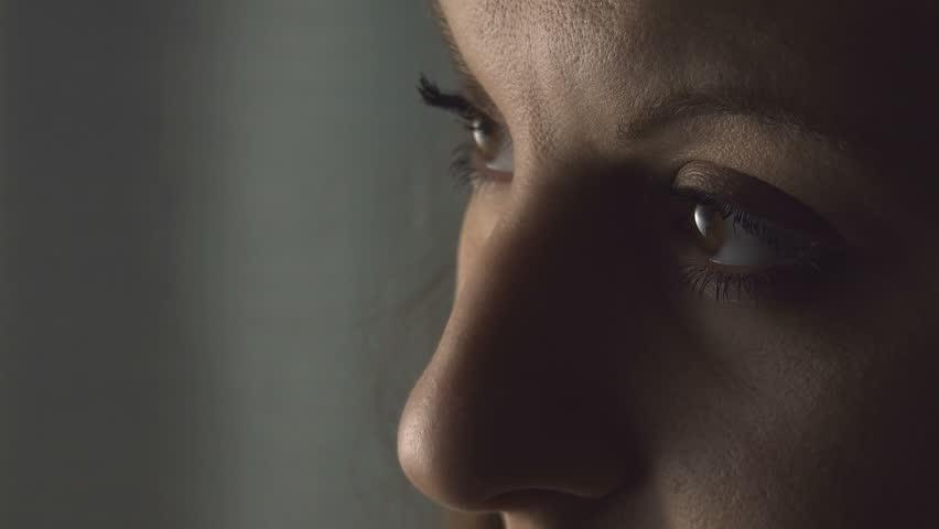 sad young woman opens eyes; sad and melancholy look, closeup portrait