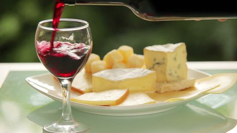 Red wine is poured into a glass on a background of cheese plate