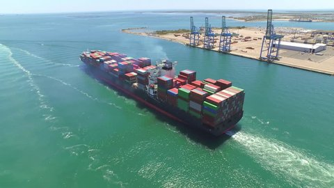 AERIAL: Container ship, loaded with shipping freight containers leaving port, freight transportation