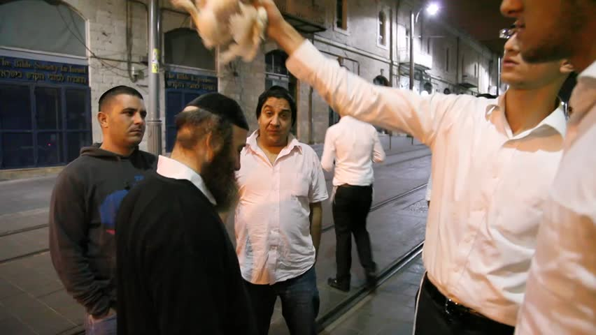 JERUSALEM - OCTOBER 06: Orthodox Jew swings a live chicken over one's head three times during Kapparot, a Jewish ritual practiced by some Jews on the eve of Yom Kippur on October 06 2011 Jerusalem, Israel.  | Shutterstock HD Video #1527902
