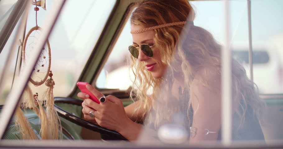 Road Trip Blonde boho girl sitting in a parked retro van at beach while looking at her phone and smiling