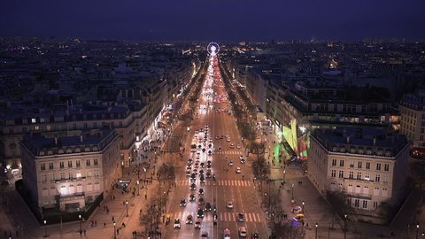 Aerial night view of Paris from the top of the Arc de Triomphe along the Champs Elysees boulevard towards the famous ferris wheel of the Place de la Concorde