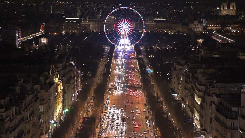 Aerial night view of the famos ferris wheel of the Place de la Concorde in Paris as seen from the top of the Arc de Triomphe along the Champs Elysees boulevard. Vertical pan going up on the street. | Shutterstock HD Video #15323893