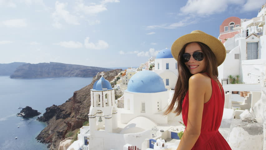 Beautiful young woman enjoying her vacation On Santorini. Happy tourist is wearing sunhat, sunglasses and red dress standing by traditional whitewashed buildings, Oia, Santorini, Greece, Europe.