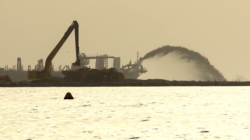 DUBAI, UNITED ARAB EMIRATES - JUNE 02, 2013: Tugboat sail against artificial island land fill, power dredger stream at background. Development area, land reclamation in progress, dark silhouettes.