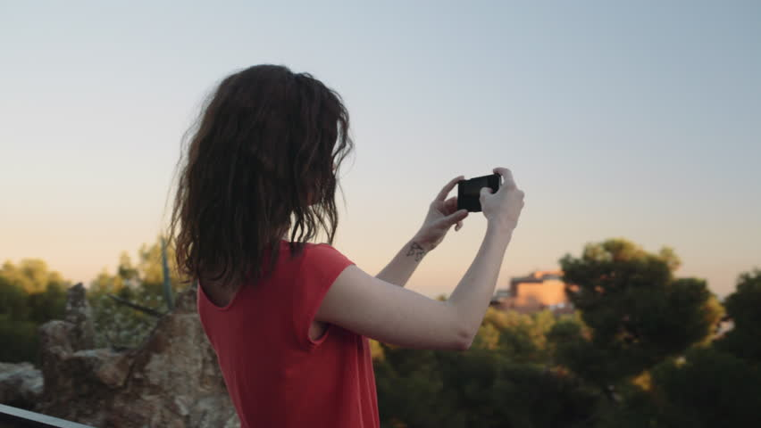 Young adult woman taking picture on mobile phone in Barcelona | Shutterstock HD Video #15343081