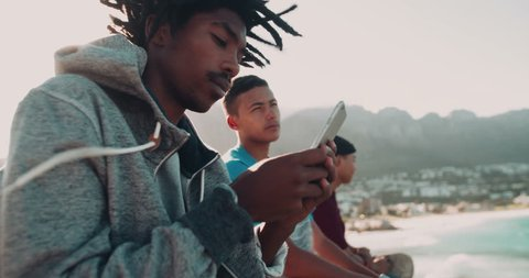 African American looks at smartphone and sits outside while mixed race friend sits beside him at the seaside during sunset
