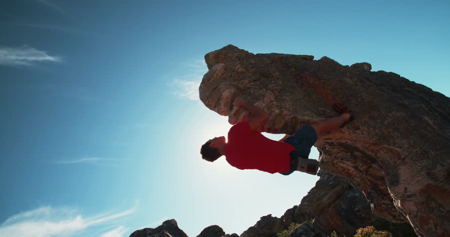 Low angle of strong rock climbing man hanging free on rock with sunflare against blue sky.