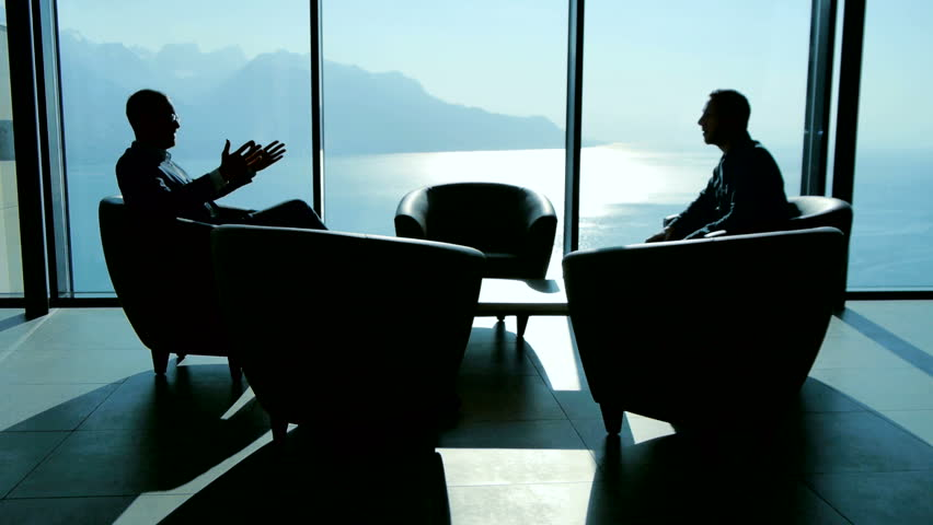 Business Meeting Of Two Professionals In Modern Lobby Lounge At Sunset Panoramic Window View Background