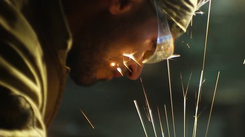 Master works on metal grinder in the workshop. Building a custom motorcycle. Sparks from the grinding wheel.