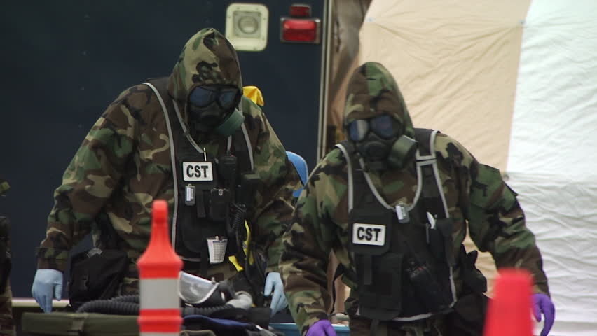 Homeland Security HAZMAT team members waling in protective suits during a nuclear or biological disaster preparedness drill.