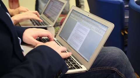 Hands of two men typing on laptops during conference