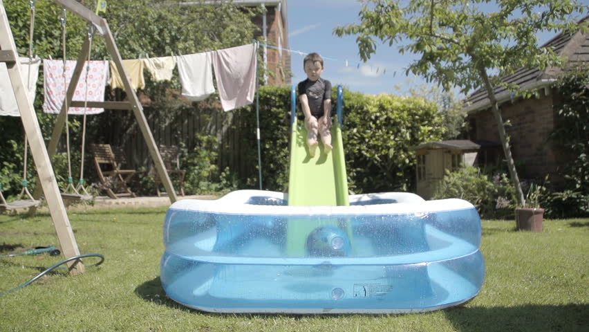 Little Boy Having Fun In A Paddling Pool In Slow Motion. A little boy is enjoying a hot summers day playing in the back garden with a slide and a paddling pool