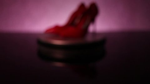 Camera closing in on rotating red, glossy stiletto high heel shoes on shop display with light increasing in intensity
