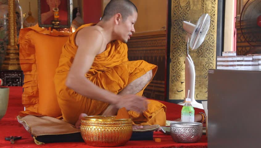 BANGKOK, THAILAND - SEPTEMBER 19: Buddhist monk drinks water in buddhist temple, September 19, 2011 in Bangkok. Buddhist monks and nuns are responsible for preserving and teaching